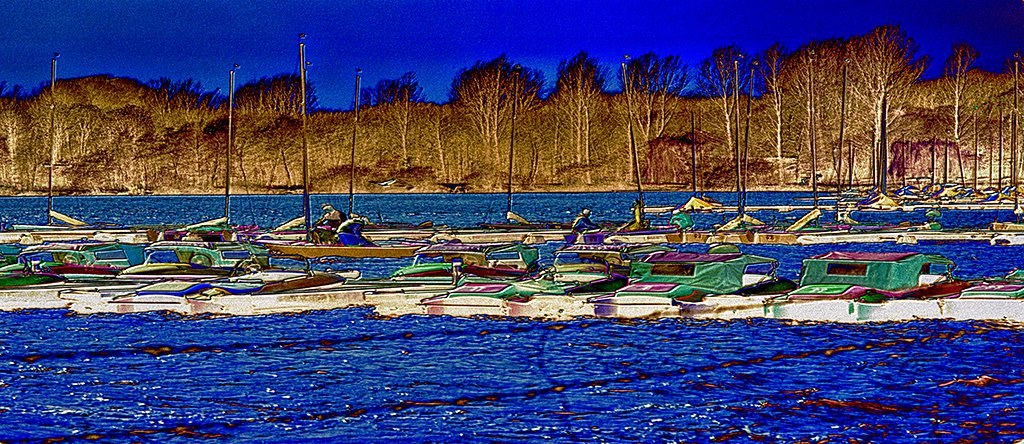 Autumn On The Lake - a panoramic depiction of an afternoon scene of strong colours on a lake with boats in late autumn